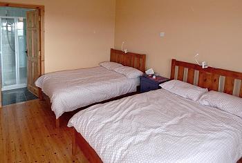 Une chambre double (avec salle de bains privée) avec deux lits doubles au rez-de-chaussée